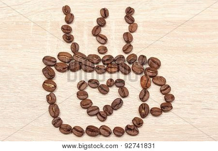 Cup Of Coffee Beans With Heart Shape. Wooden Background