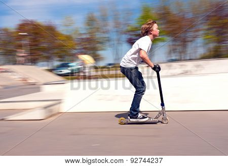 Boy Riding With Speed On His Scooter