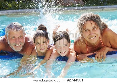 Grandparents With Grandchildren On Airbed In Swimming Pool