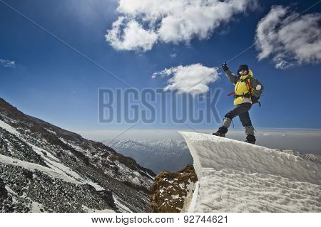 man standing on a snow cornice in mountain sunrise