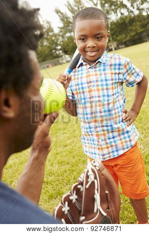 Father And Son Playing Baseball In Park