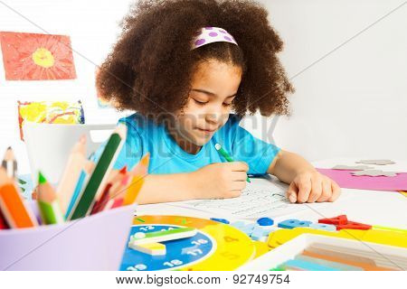 Small African girl writing letters on the paper