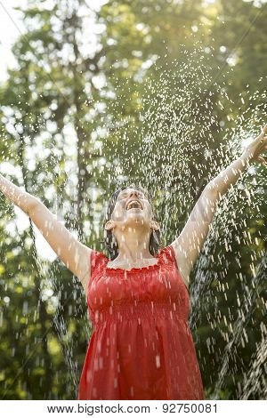 Laughing Woman Standing Under A Spray Of Water