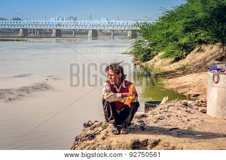 Indian Man Sitting By The River Ganges After He Did Laundry In The Water,india