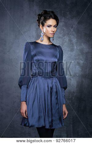 Young and beautiful fashion model posing in a cyan dress