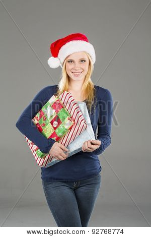 A blonde model holding holiday packages in a studio environment