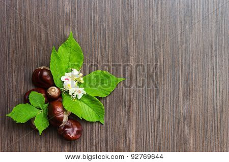 Chestnuts On A Wooden Table With Leaves And Flowers.useful As Background