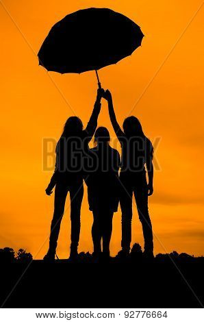 Three girl friends under an umbrella, silhouetted against the sunset