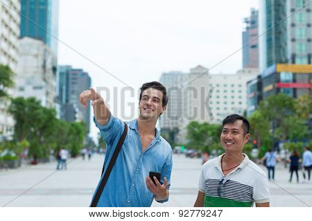 Two men tourists smile point finger sightseeing, asian mix race