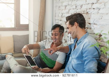 Two Men Using Tablet Computer Internet at Cafe