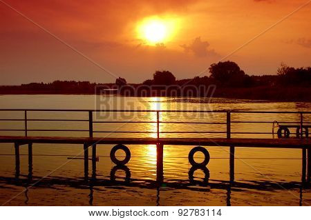 silhouette of a wooden bridge at sunset