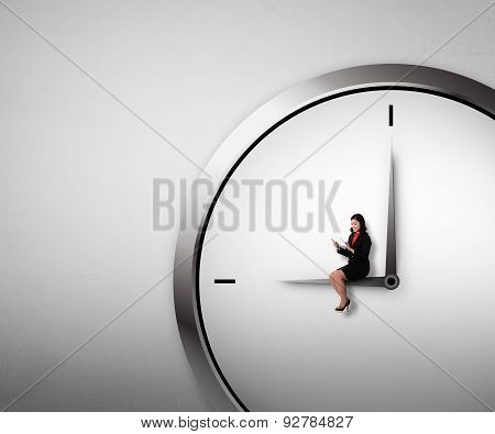 Woman Sitting On The Clock Using Tablet