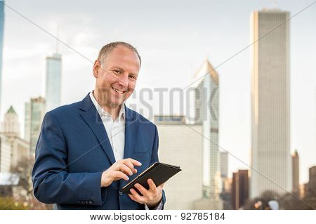 Businessman with tablet in front of office buildings