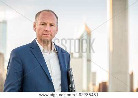 Businessman with laptop in front of office buildings
