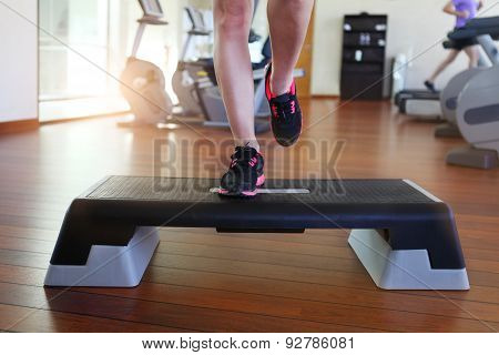 Woman Doing Step Aerobics While In Health Club