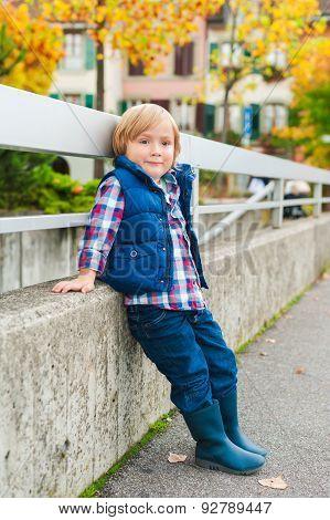 Autumn portrait of a cute little boy, wearing blue waistcoat and rain boots