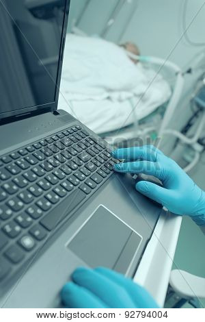 Doctor Working On Laptop In The Intensive Care