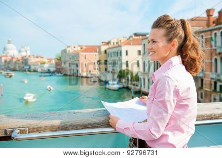 Smiling Woman In Profile Holding Map On Bridge Above Grand Canal