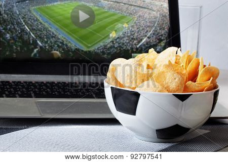 football bowl of chips at a computer with video broadcast sports fan