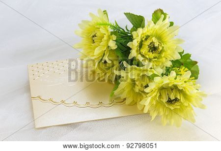 Invitation Card And A Bouquet Of Artificial Flowers On White Tulle