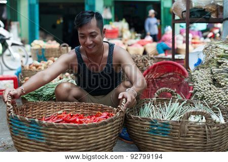 Asian man street market sell basket red chilly pepper