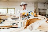 picture of carpenter  - Carpenter working with electrical grinding machine on table - JPG