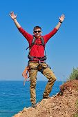 stock photo of mountain-climber  - happy climber with backpack on top of mountain - JPG