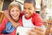 stock photo of pre-adolescent child  - Two Boys Sitting On Bench In Mall Taking Selfie - JPG