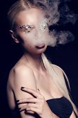stock photo of fantastic  - fashion studio portrait of beautiful sexy woman with blond hair with fantastic makeup with bijou accessories posing in smoke - JPG