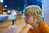 stock photo of boys night out  - cute boy smiles tired while sitting outside by night next to the street - JPG
