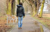 stock photo of lonely woman  - Elegant lonely woman walking in autumn park on cold rainy day sad woman in park