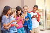 foto of pre-adolescent child  - Group Of Children Sitting In Mall Using Mobile Phones - JPG