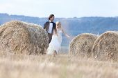 stock photo of hay bale  - Young married couple playing like kids running between hay bales - JPG