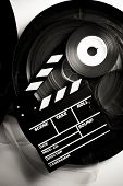 stock photo of mm  - Movie clapper board on 35 mm movie reels in vintage black and white vertical frame - JPG