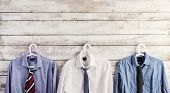 stock photo of composition  - Fathers day composition of shirts and ties hang on wooden wall background - JPG