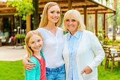 stock photo of family bonding  - Three generations of family women bonding to each other and smiling while standing in front of their house  - JPG