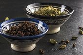 stock photo of cardamom  - two ceramic bowls full of spices - JPG