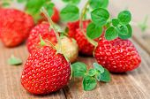 pic of oregano  - Fresh tasty strawberries with oregano on wooden table selective focus - JPG