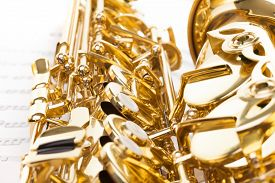 pic of musical scale  - Detailed view of keys and body of shiny golden alto saxophone on the musical notes background with standard scales exercises - JPG