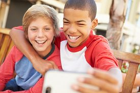 foto of pre-adolescents  - Two Boys Sitting On Bench In Mall Taking Selfie - JPG