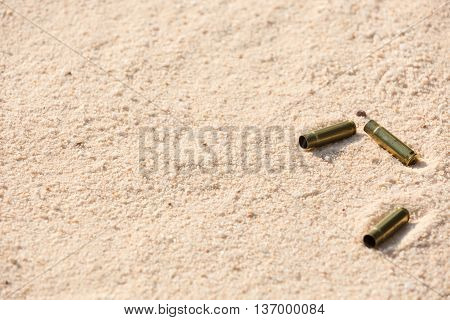 Brass casing on the beach sand in morning light