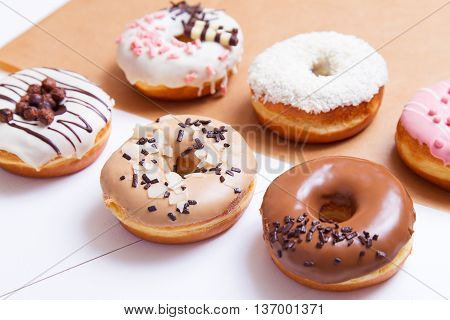 Colored delicious donuts with sprinkles on a white wooden background