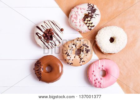 Colored donuts with sprinkles on a white wooden background