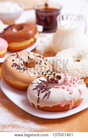 Colored delicious donuts with coffee and milk on a white wooden background
