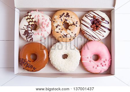 Colored donuts with glaze in a box on a white wooden background