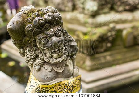 Traditional demon guards statue carved in stone in Bali island.