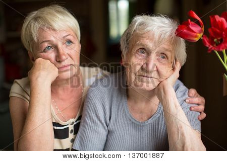 An elderly woman sits thoughtfully with an adult daughter.