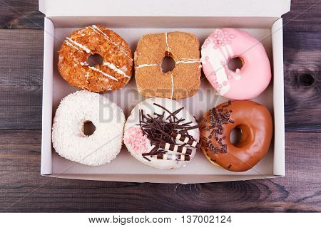 Colorful delicious donuts with glaze and sprinkles in a box on a dark wooden table. Top view with copy space