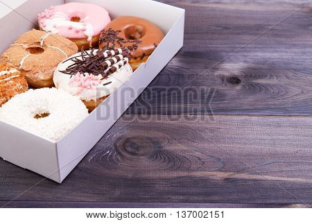 Delicious donuts with colorful glaze and sprinkles in a box on a dark wooden background.