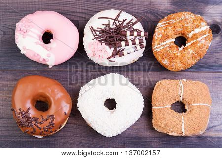 Colorful delicious donuts with chocolate coconut and other sprinkles on a dark wooden background. Top view